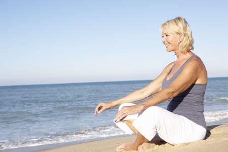 mujer meditando: Mujer Senior en ropa de Fitness meditando en Playa