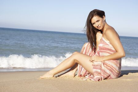 Young Woman Relaxing On Beach Wearing Wrap photo