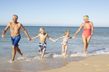 grandmother and grandson: Grandparents With Grandchildren Enjoying Beach Holiday Together