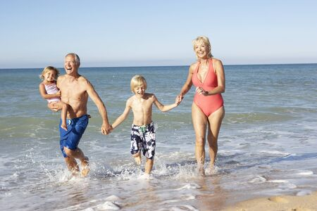 Grandparents With Grandchildren Enjoying Beach Holiday Together photo