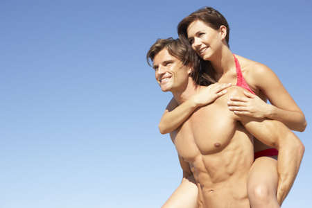 bikini couple: Young Couple Enjoying Piggyback On Beach Holiday Stock Photo