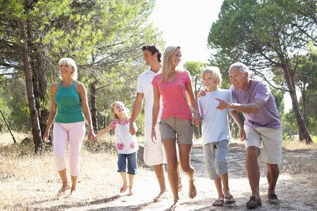 A family, with parents, children and grandparents, walk through park photo