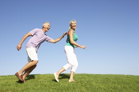 tercera edad: Senior pareja aunque campo en ejecuci�n Foto de archivo