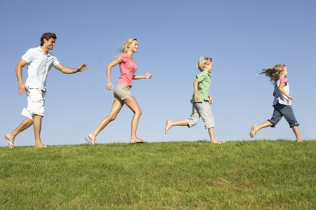 Young family, parents with children,  running through field Stock Photo - 8510209