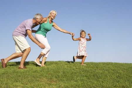 Senior couple, with granddaughter,  running though field Stock Photo - 8513921