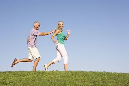 Senior couple running though field photo
