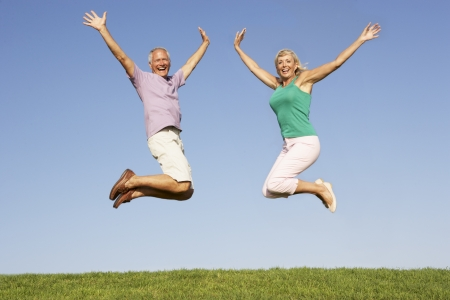 Senior couple jumping in air photo