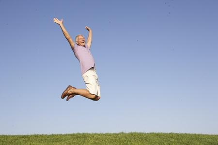 persona saltando: Senior hombre saltando en el aire