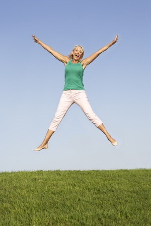 Senior woman  jumping in air photo