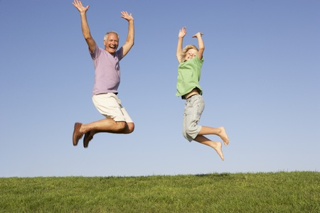 Senior man with grandson jumping in air photo