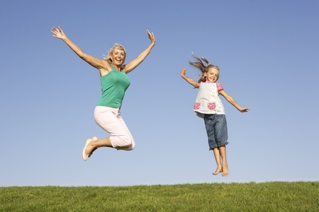 Senior woman with granddaughter jumping in air Stock Photo - 8514126