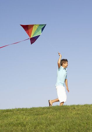 kite flying: Young boy runs with kite through field
