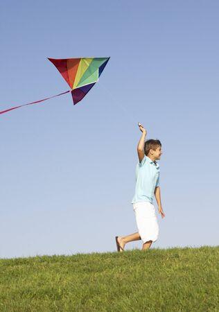 the runs: Young boy runs with kite through field