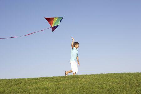 凧: 若い男の子はフィールドを介してカイトと実行します。