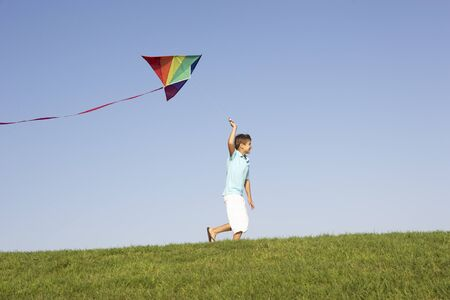 flying a kite: Young boy runs with kite through field