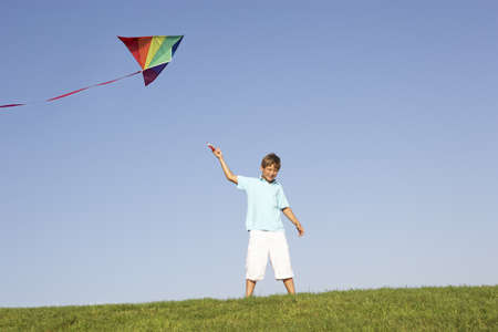 Young boy poses with kite in a field photo