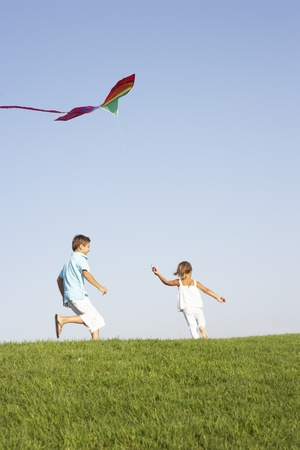 Young children run with kite through field Stock Photo - 8510118