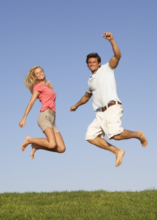 fit couple: Young couple jumping in air