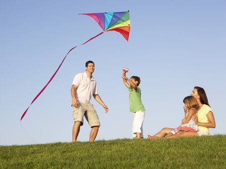 flying man: Young family, parents with children,  playing in a field