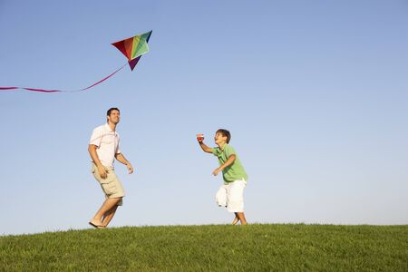 man flying: Young parent, father with child, playing in a field