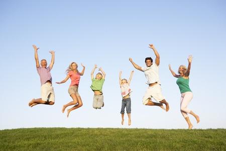 personas saltando: J�venes parejas con abuelos y ni�os saltan en un campo Foto de archivo