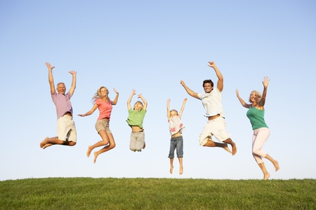 3 generation: Young couple with grandparents and children jump in a field