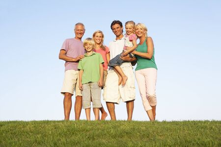 three generation: A family, with parents, children and grandparents, posing in a field
