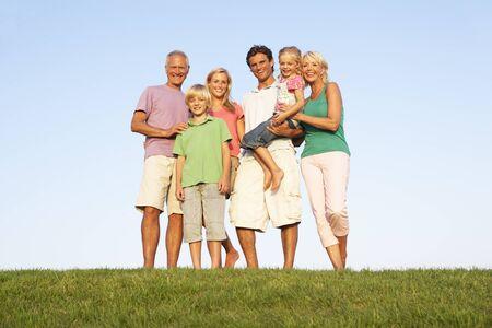 Une famille, avec les parents, les enfants et les grands-parents, posant dans un champ Banque d'images