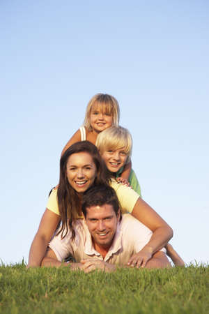 Young parents, with children, posing on a field photo