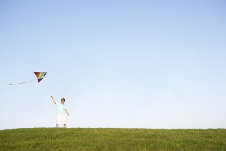 Young boy flying kite in a field photo