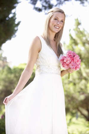 bouqet: Bride Wearing Dress Holding Bouqet At Wedding