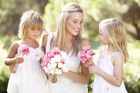 arm bouquet: Bride With Bridesmaids Outdoors At Wedding