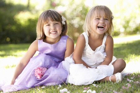 bridesmaid: Two young girls posing in park Stock Photo