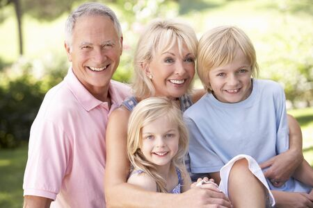 Senior couple with children posing in park Stock Photo - 8514459