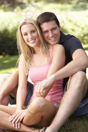 Portrait Of Young Couple Relaxing In Park photo