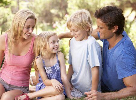 Padres j�venes con ni�os hablando en un parque Foto de archivo - 8505180