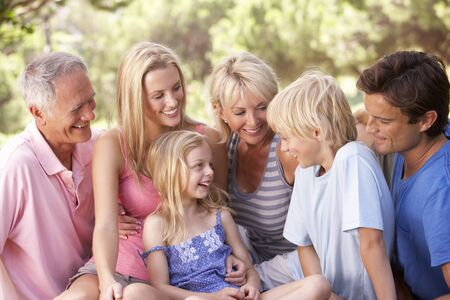 three generation: A family, with parents, children and grandparents, relaxing in a park Stock Photo