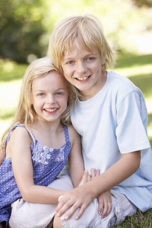 7 year old girl: Brother and sister pose in a park Stock Photo