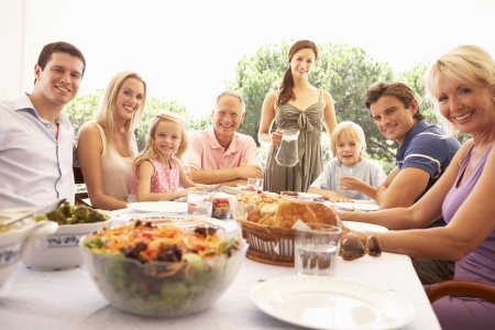 eating in the garden: A family, with parents, children and grandparents, enjoy a picnic
