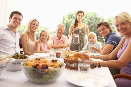 familia comiendo: Una familia, con los padres, hijos y abuelos, disfrutar de un picnic Foto de archivo