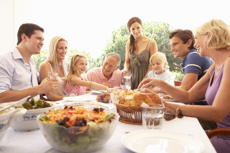 famiglia in giardino: Una famiglia, con i genitori, bambini e nonni, gode di un picnic