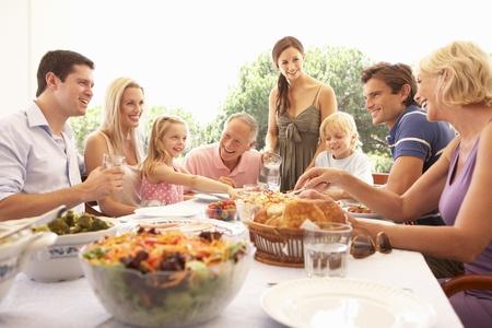 familia comiendo: Una familia, con los padres, hijos y abuelos, disfruta de un picnic Foto de archivo