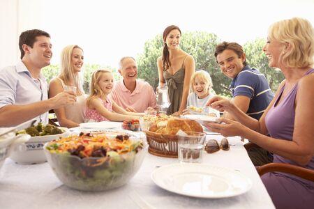 hombre comiendo: Una familia, con los padres, hijos y abuelos, disfruta de un picnic Foto de archivo