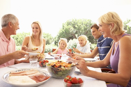children eating: Extended family, parents, grandparents and children, eating outdoors Stock Photo