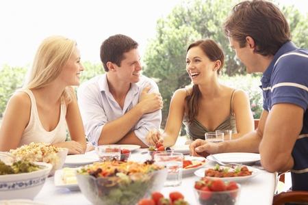 hombre comiendo: Dos j�venes parejas comer al aire libre Foto de archivo
