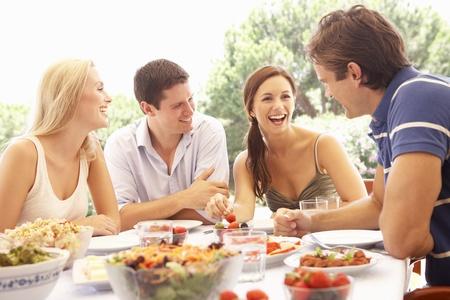 hombre comiendo: Dos parejas j�venes comer al aire libre Foto de archivo