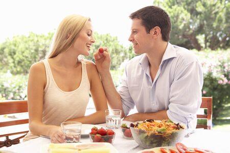 hombre comiendo: Joven pareja comer al aire libre