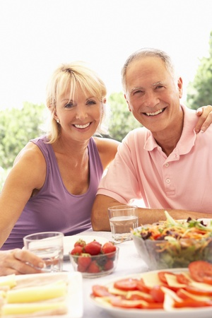 Senior couple eating outdoors photo