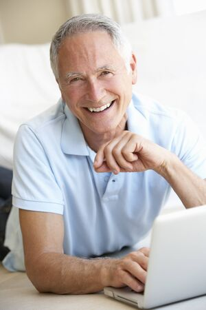 Senior man using laptop computer photo