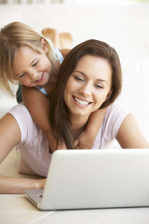 mom and child: Young woman with girl using laptop computer